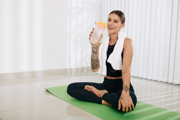 Porträt der freudigen jungen sportlerin, die auf yogamatte sitzt und frisches wasser nach dem training genießt