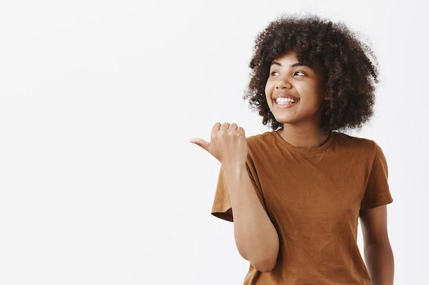 Porträt der freudigen verträumten und sorglosen jungen afroamerikanerfrau mit dem lockigen haar, das mit dem daumen schaut und nach links zeigt, der von guten erinnerungen lächelt