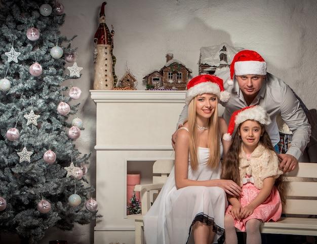 Porträt der freundlichen familie, die kamera am weihnachtsabend betrachtet