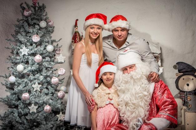 Porträt der freundlichen familie, die kamera am weihnachtsabend und weihnachtsmann betrachtet