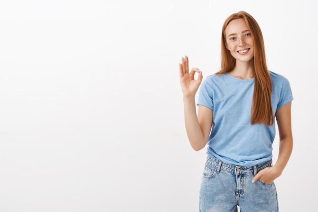 Porträt der freundlichen und freudigen gutaussehenden rothaarigen frau mit sommersprossen, die hand in der tasche halten, lässiges gespräch, das sicherstellt, dass die arbeit rechtzeitig erledigt wird und okay oder ausgezeichnete geste zeigt