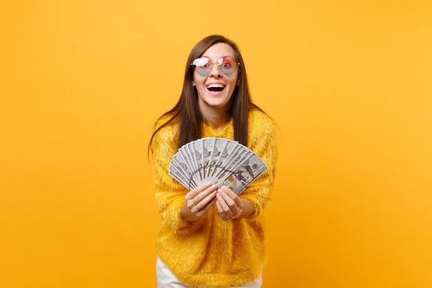 Porträt der fröhlich lächelnden jungen frau in den herzbrillen, die bündel viele dollarbargeld einzeln auf hellgelbem hintergrund halten. menschen aufrichtige emotionen, lifestyle-konzept. werbefläche.