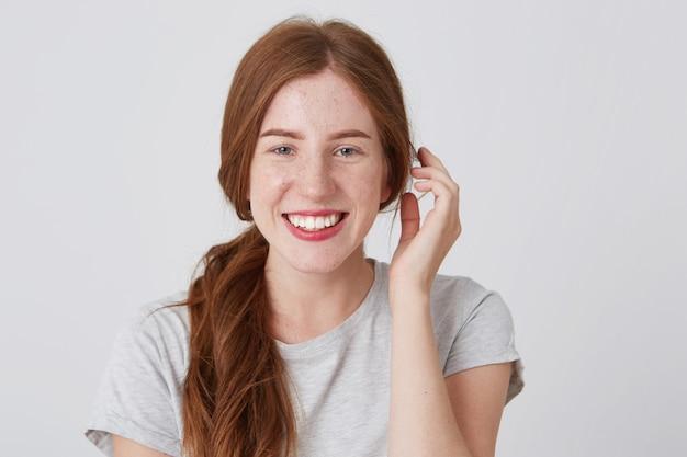 Porträt der fröhlichen attraktiven jungen frau mit roten haaren und sommersprossen fühlt sich glücklich und lächelnd