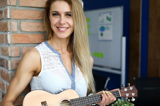 Porträt der fröhlichen blonden frau, die ukulele hält