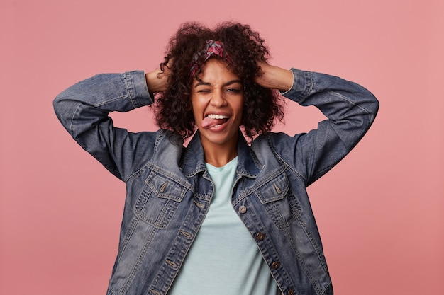 Porträt der fröhlichen dunkelhäutigen lockigen brünetten dame im bunten stirnband, die erhobene hand auf ihrem kopf hält, während sie freudig zwinkert und ihre zunge zeigt, isoliert
