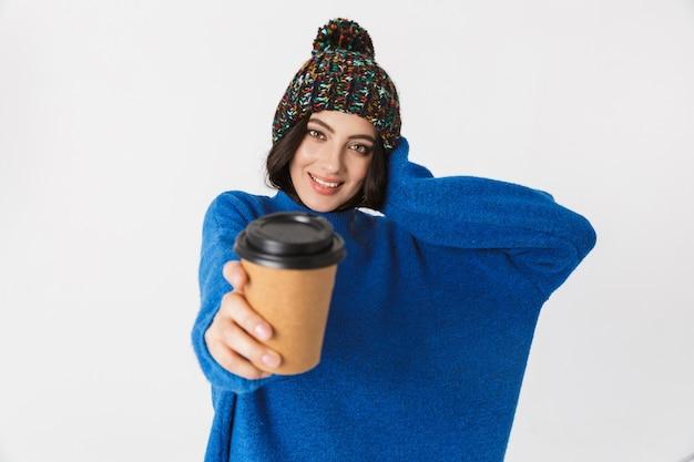 Porträt der fröhlichen frau, die wintermütze trägt, die lächelt und kaffee zum mitnehmen im stehen trinkt, lokalisiert auf weiß