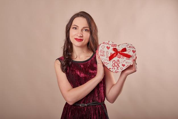 Porträt der fröhlichen frau im roten kleid, das geschenkbox hält