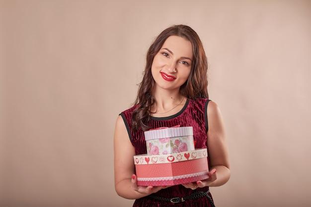 Porträt der fröhlichen frau im roten kleid, das geschenkboxen hält