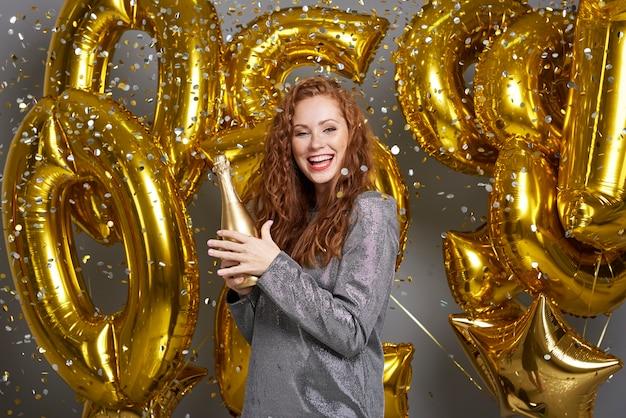 Porträt der fröhlichen frau mit champagner unter der dusche des konfettis