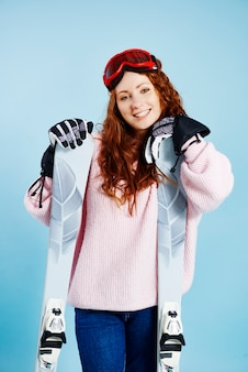 Porträt der fröhlichen frau mit ihren skiern