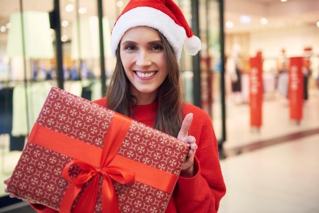 Porträt der fröhlichen frau mit weihnachtsgeschenk