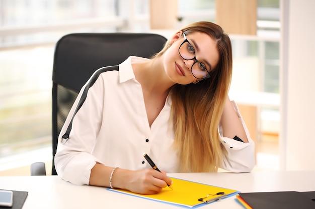 Porträt der fröhlichen geschäftsfrau, die auf vertrag schreibt, der am schreibtisch im büro sitzt