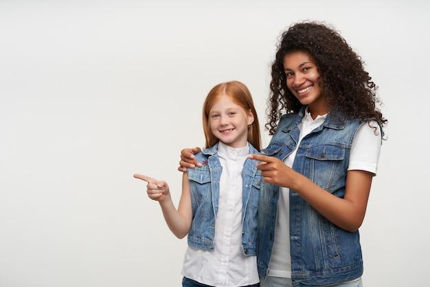 Porträt der fröhlichen hübschen jungen dunkelhäutigen brünetten frau, die niedliche rothaarige freudige kleine dame umarmt und mit zeigefinger beiseite zeigt, lokalisiert auf weiß