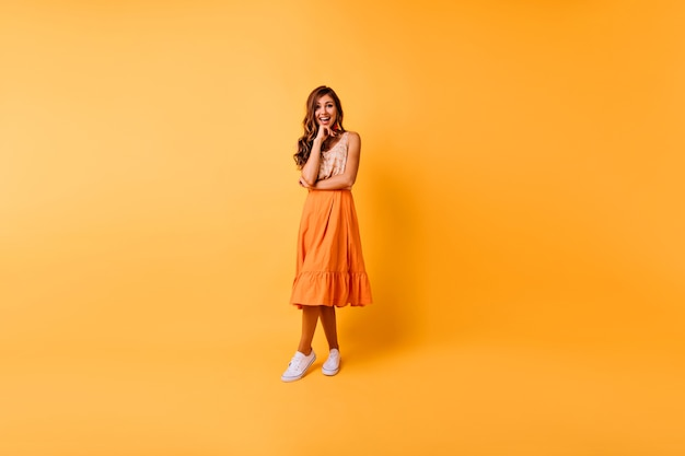 Porträt der fröhlichen ingwerfrau in voller länge. romantisches kaukasisches mädchen in den orangefarbenen kleidern