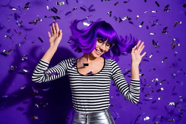 Porträt der fröhlichen jugend, die die handflächen der erhabenen hände über lila violettem hintergrund winkend anhebt