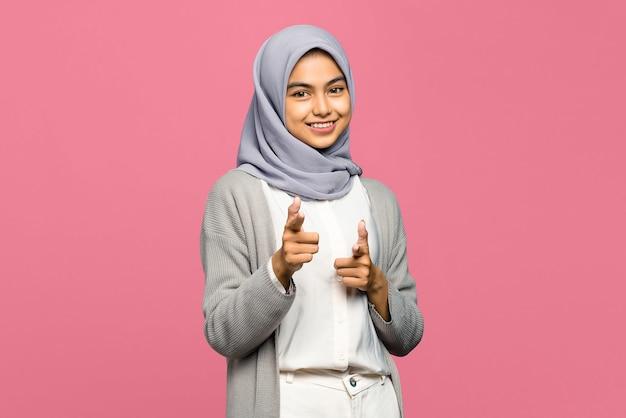 Porträt der fröhlichen jungen asiatischen frau, die finger zur kamera mit lächelndem gesicht zeigt