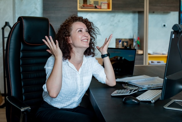 Porträt der fröhlichen jungen büroangestelltenfrau, die glücklich und aufgeregt mit erhobenen armen sitzt, die fröhlich im büro lächelnd sitzen