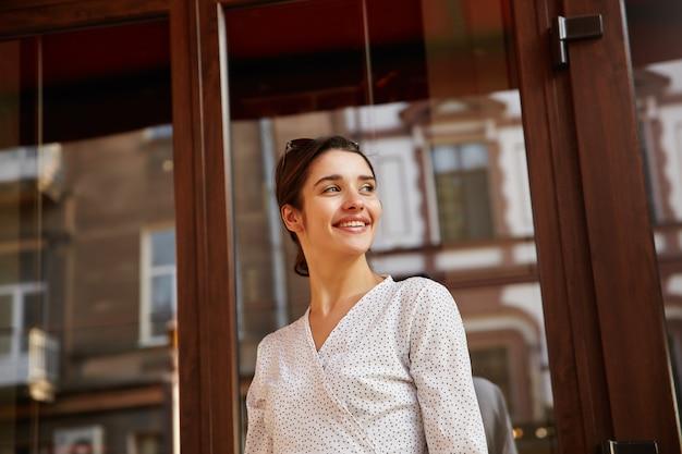 Porträt der fröhlichen jungen dunkelhaarigen dame mit brötchenfrisur, die an sonnigem warmem tag über städtische umgebung geht, in guter stimmung ist und angenehm lächelt