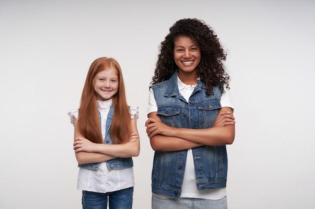 Porträt der fröhlichen jungen dunkelhäutigen brünetten frau und des langhaarigen hübschen rothaarigen mädchens, die hände kreuzen, während sie auf weiß stehen und glücklich lächeln