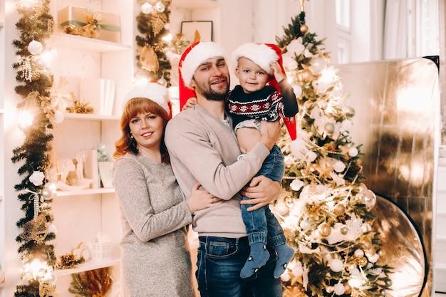 Porträt der fröhlichen jungen familie in den weihnachtsmützen, die neujahr zu hause feiern