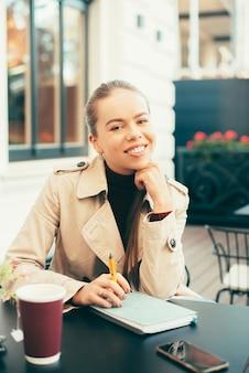 Porträt der fröhlichen jungen frau, die im café sitzt und zeit hat, um tasse tee zu trinken