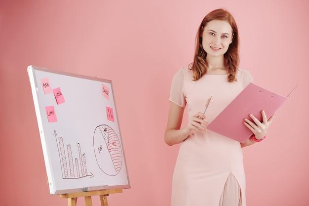 Porträt der fröhlichen jungen geschäftsfrau, die am whiteboard steht, wenn präsentation für kollegen durchführt