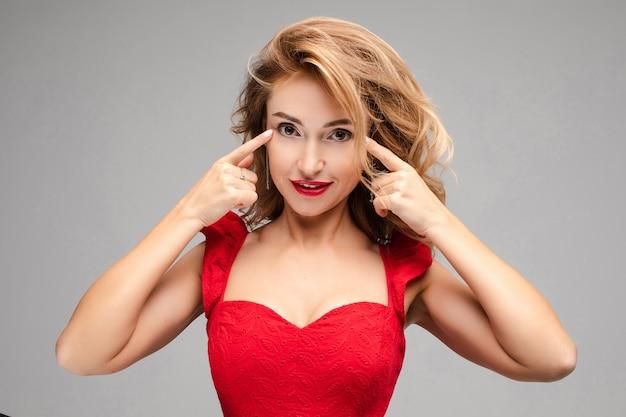 Porträt der fröhlichen jungen kaukasischen frau mit langen blonden haaren, hellem make-up, roten lippen im roten kleid gestikuliert und empfiehlt, über etwas nachzudenken
