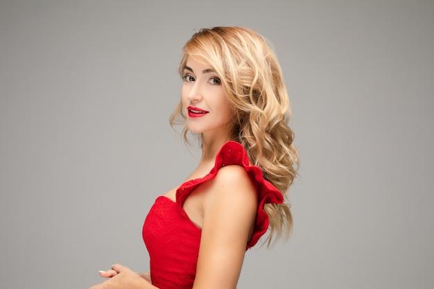 Porträt der fröhlichen jungen kaukasischen frau mit langen blonden haaren, hellem make-up, roten lippen im roten kleid lächelt