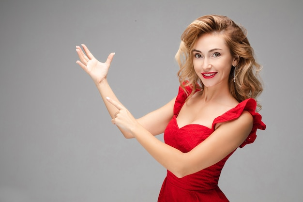 Porträt der fröhlichen jungen kaukasischen frau mit langen blonden haaren, hellem make-up, roten lippen im roten kleid zeigt auf ihre hand
