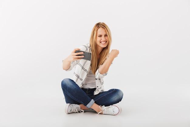 Porträt der fröhlichen jungen lässigen frau, die handy betrachtet