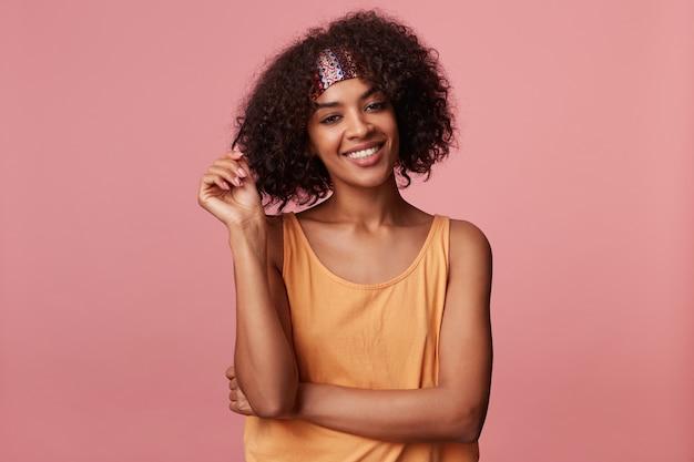 Porträt der fröhlichen jungen lockigen brünetten frau mit der dunklen haut, die ihr haar zieht, während sie mit breitem aufrichtigem lächeln schaut und helloranges hemd trägt