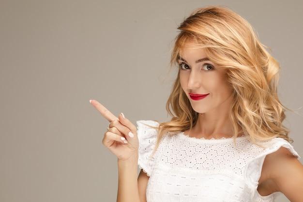 Porträt der fröhlichen kaukasischen frau mit langen blonden haaren, hellem make-up, roten lippen im weißen kleid gestikuliert und lächelt