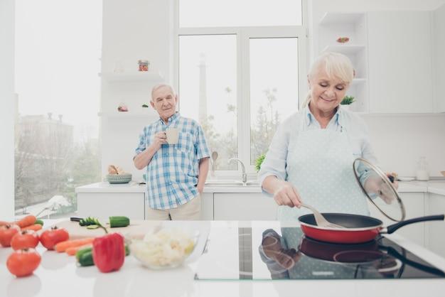 Porträt der fröhlichen konzentrierten ehegatten, die kochen