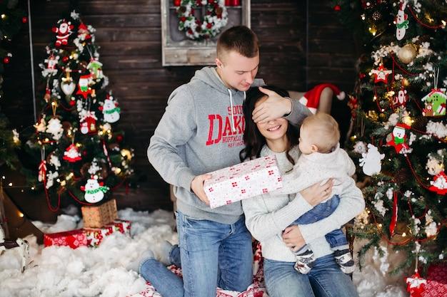 Porträt der fröhlichen liebenden familie, die weihnachtsgeschenke mit kindern am geschmückten kamin und am weihnachtsbaum auspackt