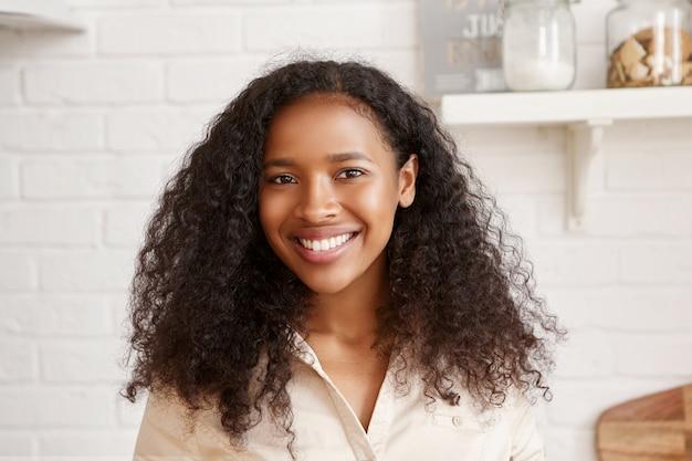 Porträt der fröhlichen positiven jungen afrikanischen frau mit den perfekten weißen zähnen, dem voluminösen schwarzen haar und der glänzenden gebräunten haut, die freizeit zu hause verbringen und in der küche mit glücklichem strahlendem lächeln posieren