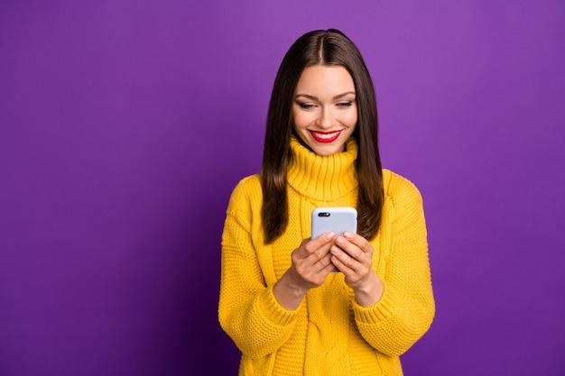 Porträt der fröhlichen positiven niedlichen hübschen netten frau, die in das telefon schaut und positive benachrichtigungen erhält, die lange erwartet werden.