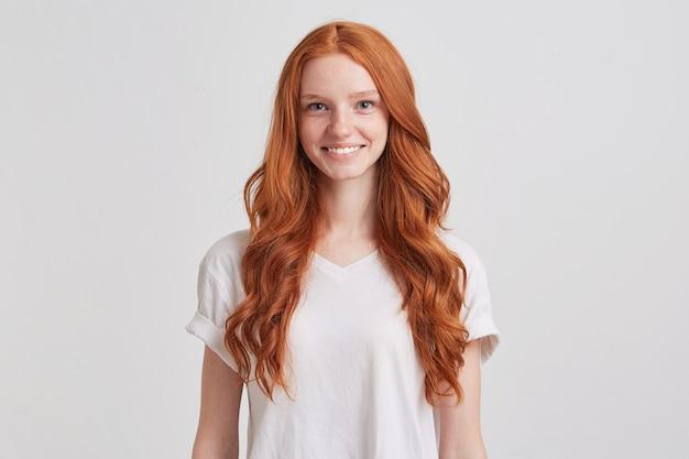 Porträt der fröhlichen schönen jungen frau mit langen welligen roten haaren