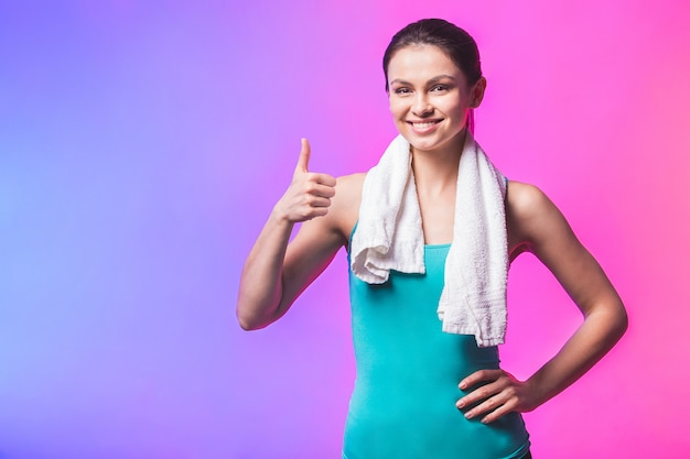 Porträt der fröhlichen selbstbewussten jungen frau mit handtuch nach turnhalle lokalisiert gegen weißen hintergrund. daumen hoch.