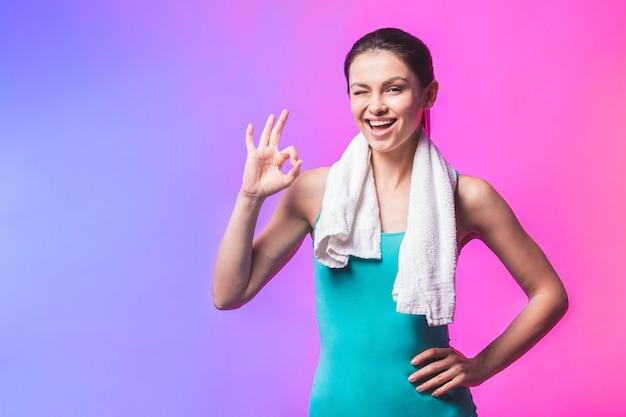 Porträt der fröhlichen selbstbewussten jungen frau mit handtuch nach turnhalle lokalisiert gegen weißen hintergrund. ok zeichen.