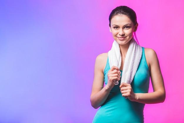 Porträt der fröhlichen selbstbewussten jungen frau mit handtuch nach turnhalle lokalisiert gegen weißen hintergrund.