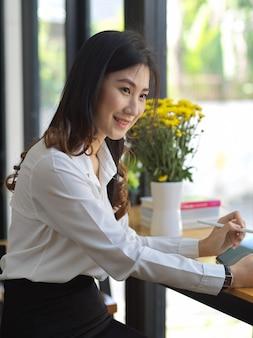 Porträt der fröhlichen studentin, die aufgabe mit digitalem tablett im café tut