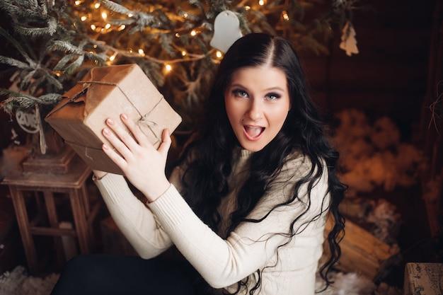 Porträt der fröhlichen und positiven frau mit dem langen dunklen haar im pullover, in den jeans und in den warmen socken, die verpacktes geschenk für weihnachten halten, während sie unter geschmücktem weihnachtsbaum sitzen