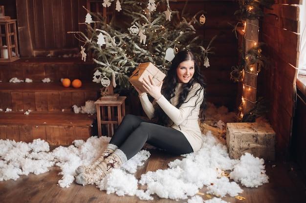 Porträt der fröhlichen und positiven frau mit dem langen dunklen haar im pullover, in den jeans und in den warmen socken, die verpacktes geschenk für weihnachten halten, während sie unter geschmücktem weihnachtsbaum und schneefall sitzen