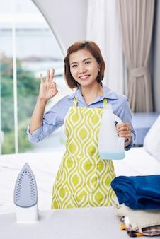 Porträt der fröhlichen vietnamesischen hausfrau mit flasche duftendem bügelwasser in der hand, die ok zeichen zeigt