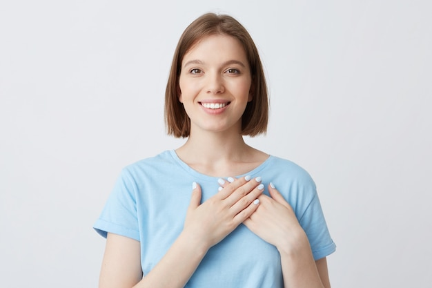 Porträt der fröhlichen zarten jungen frau trägt blaues t-shirt legte hände auf ihren herzbereich