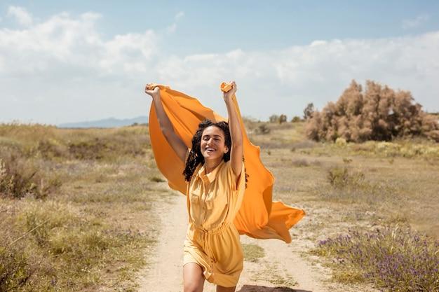 Porträt der frohen frau mit gelbem stoff in der natur