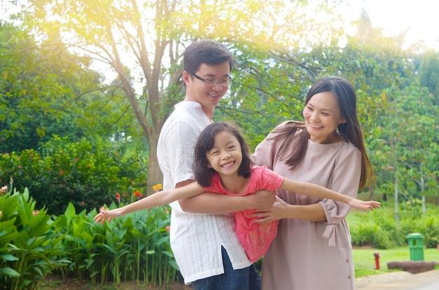 Porträt der frohen glücklichen asiatischen familie, die zusammen park am im freien während des sommersonnenuntergangs spielt.
