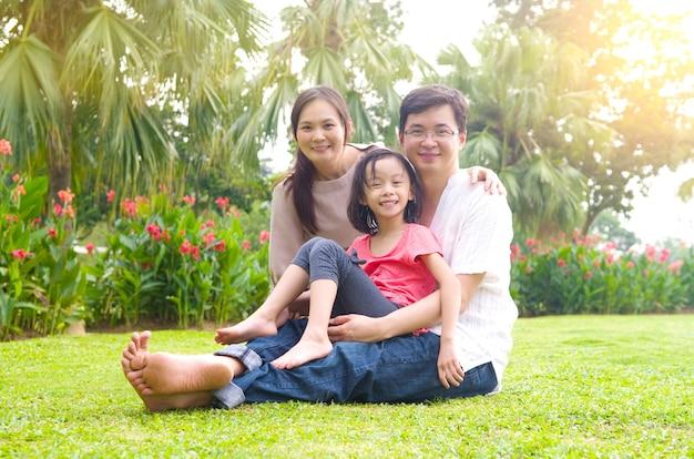 Porträt der frohen glücklichen asiatischen familie park am im freien während des sommersonnenuntergangs.