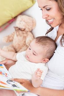 Porträt der frohen mutter ein buch zu ihrem baby lesend, das im wohnzimmer sitzt
