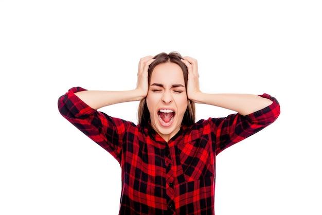 Porträt der frustrierten wütenden jungen frau, die kopf berührt und schreit